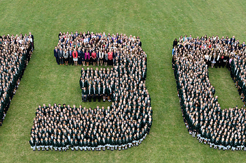 "Aerial group photograph with pupils standing in shape of the numbers ""130"""